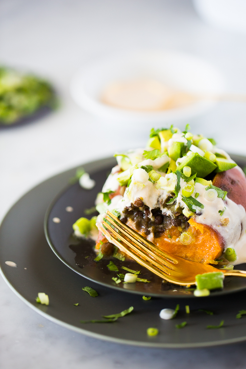 Healthy Mexican loaded sweet potatoes with lentils in salsa verde, topped with diced avocado, cashew crema, cilantro, and scallions. Yum. #vegan, #veganmexican,#authenticmexicanrecipe