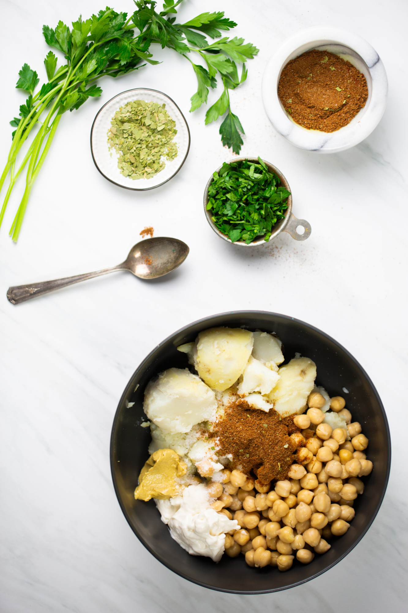 a bowl with chickpeas, potatoes and herbs