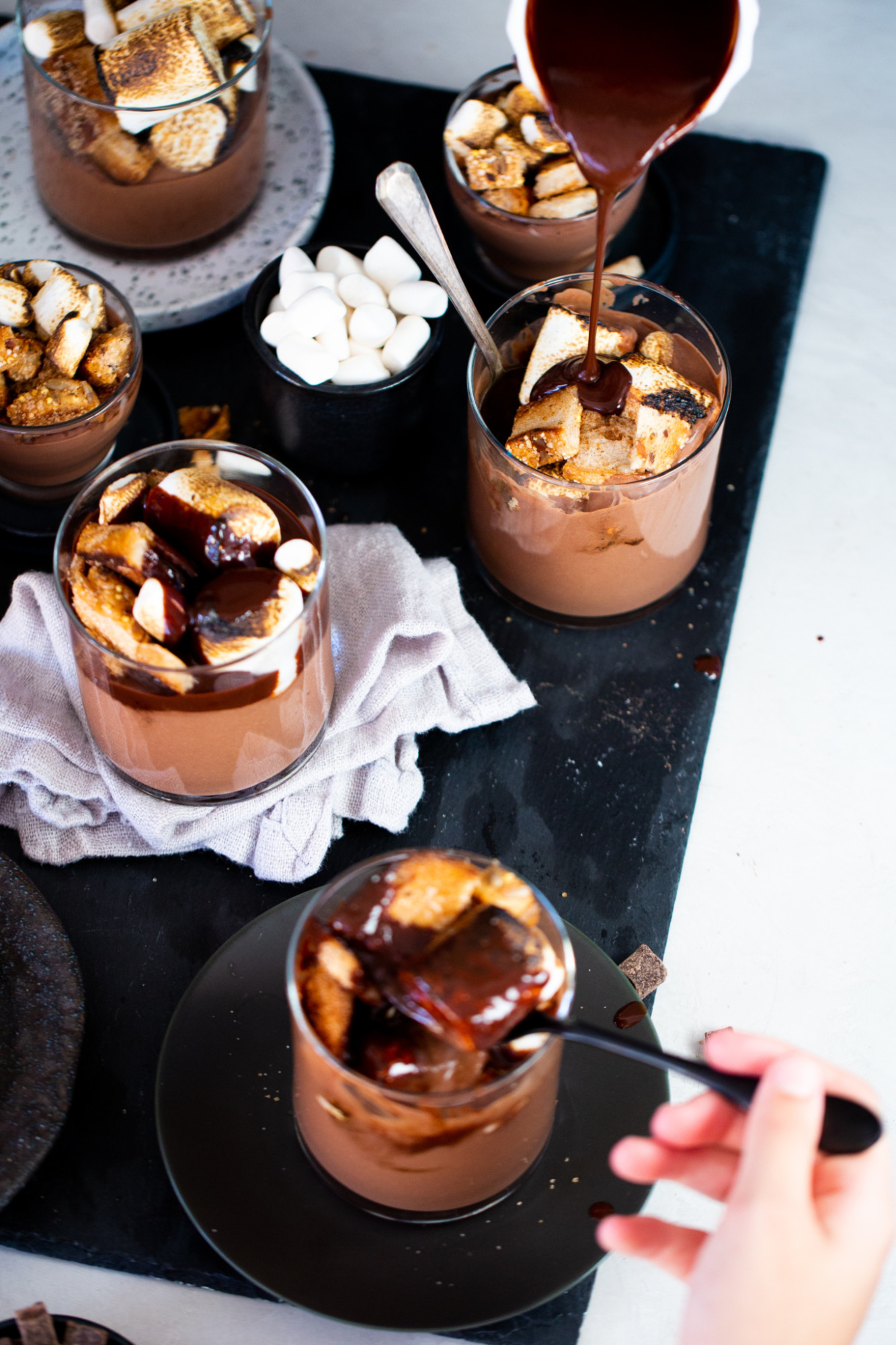 Chocolate sauce being poured over a vegan chocolate mousse.