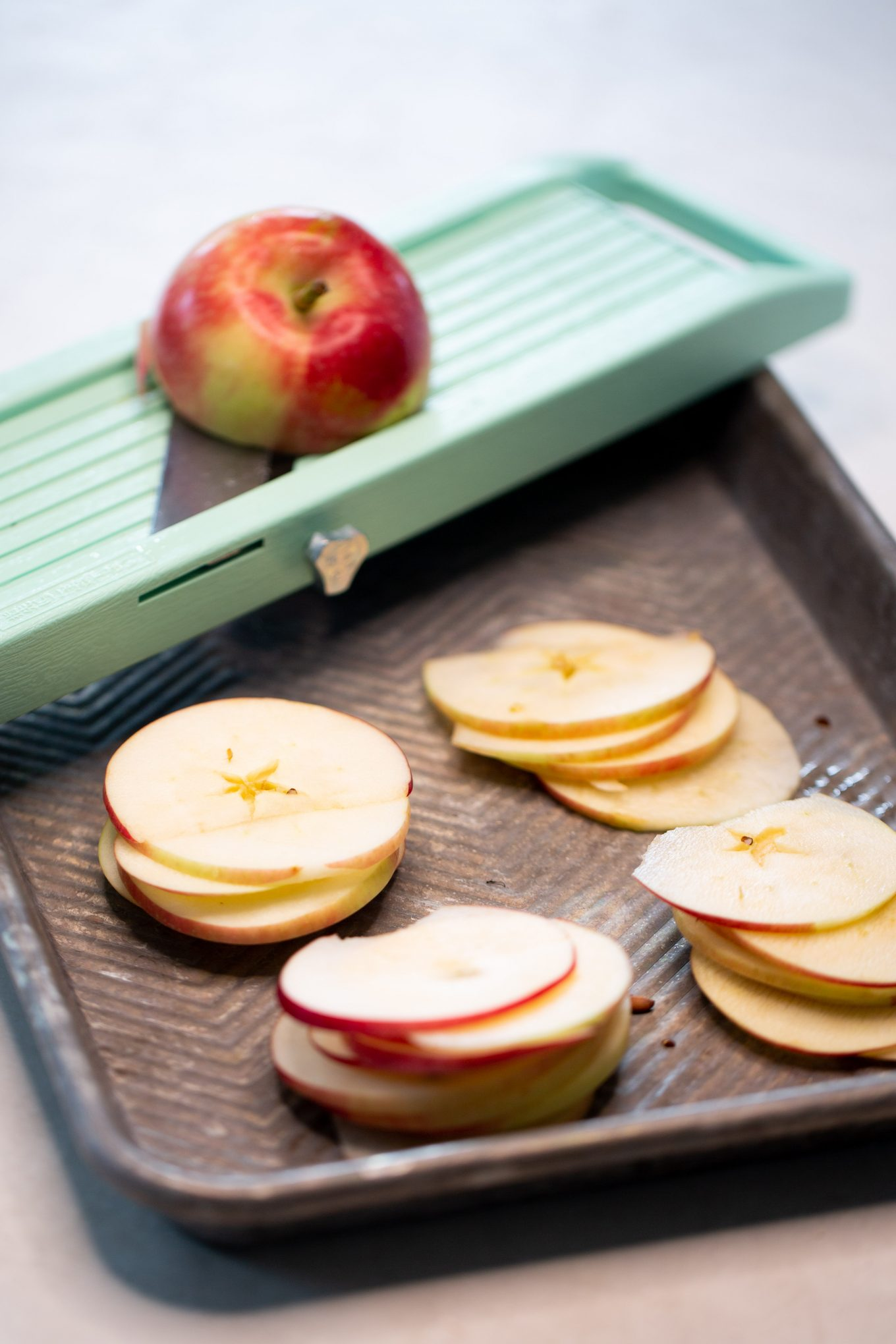Making apple chips by cutting them with a mandoline