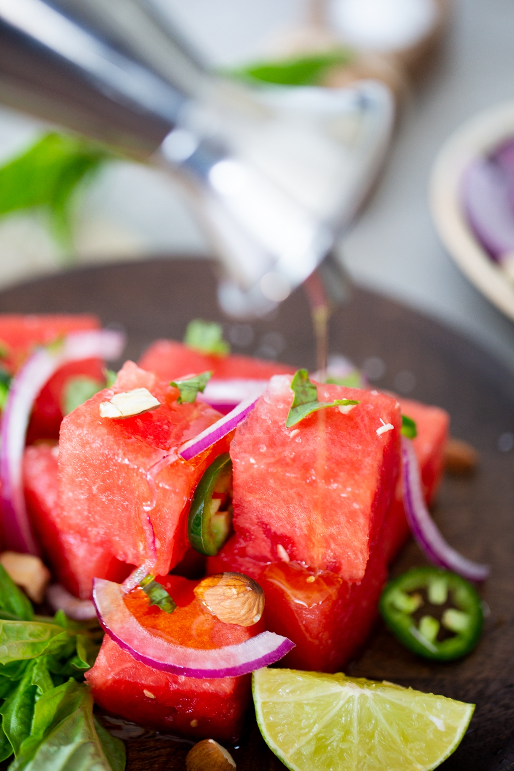 Spicy Watermelon saladbeing drizzled with olive oil .