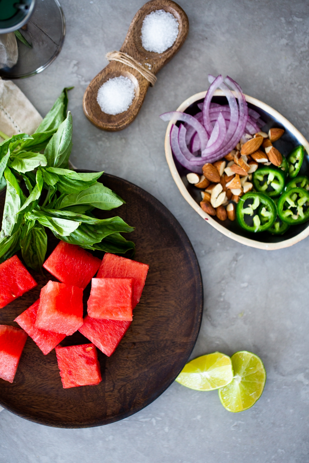 Watermelon, sliced onions, sliced chile, almonds and limes to prepare watermelon salad.