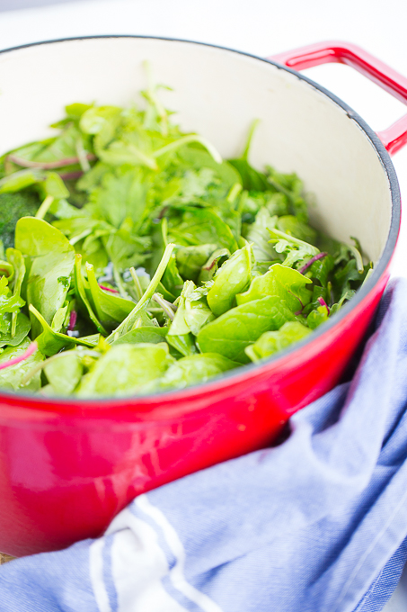 red dutch oven with greens