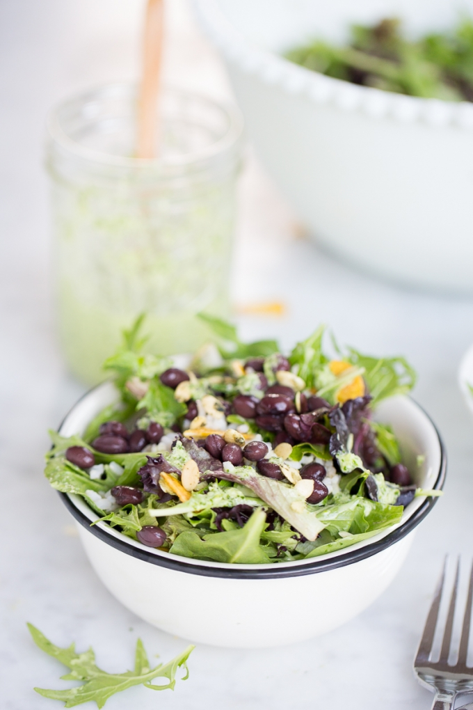 Bowl of salad with black beans, greans and rice with green vegan dressing