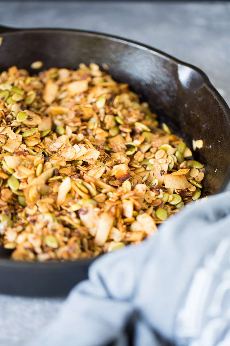 Savory and vegan granola in a glass container.in a cast iron pan