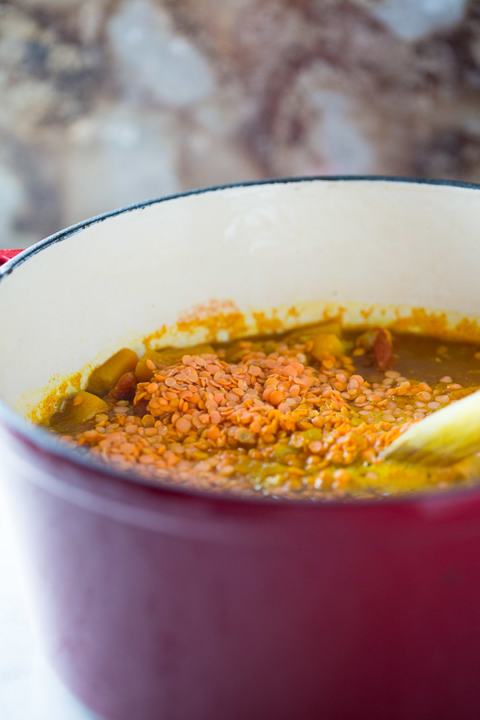 vegan red lentil soup cooking in a red dutch oven