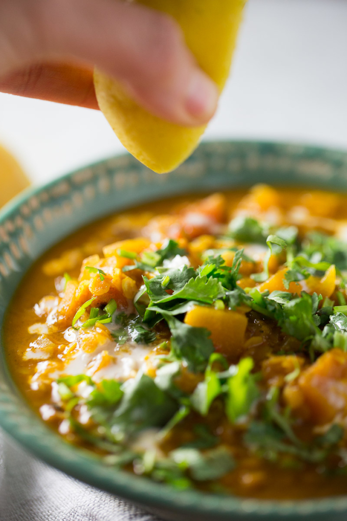 Adding some freshly squeezed lemon juice to a bowl of curried red lentil soup