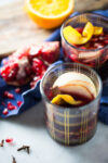 Mulled wine with apple slices and pomegranate seeds.