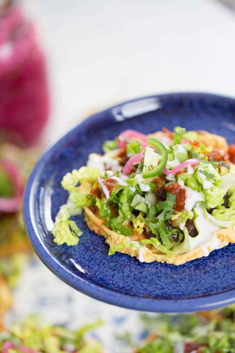Mexican sopes, homemade and vegan. Topped with beans, lettuce, crema and salsa.