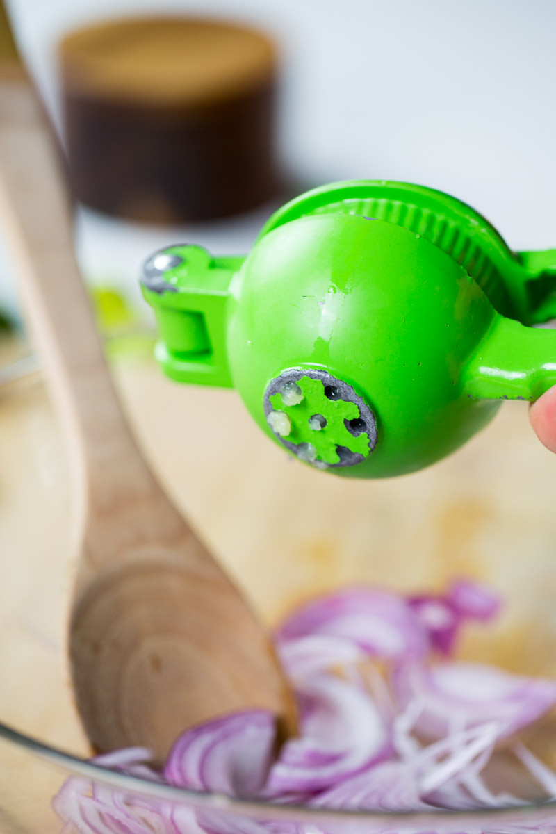 using a lime press to squeeze lime over red onion