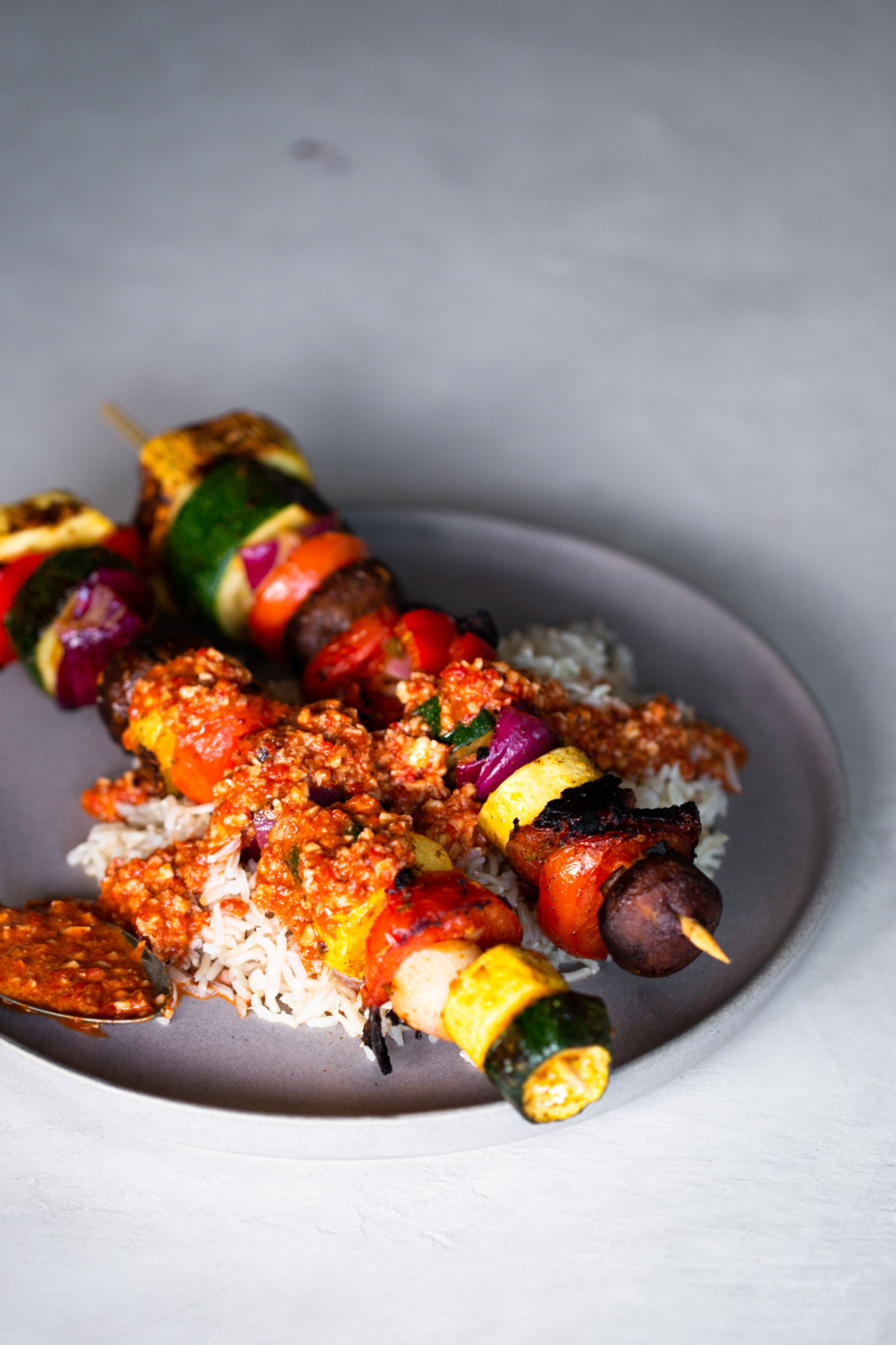 grilled vegetable kebabs over brown rice and drizzled with romesco sauce