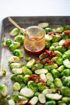 brussels spsrouts over baking sheet covered with sweet and spicy sauce.