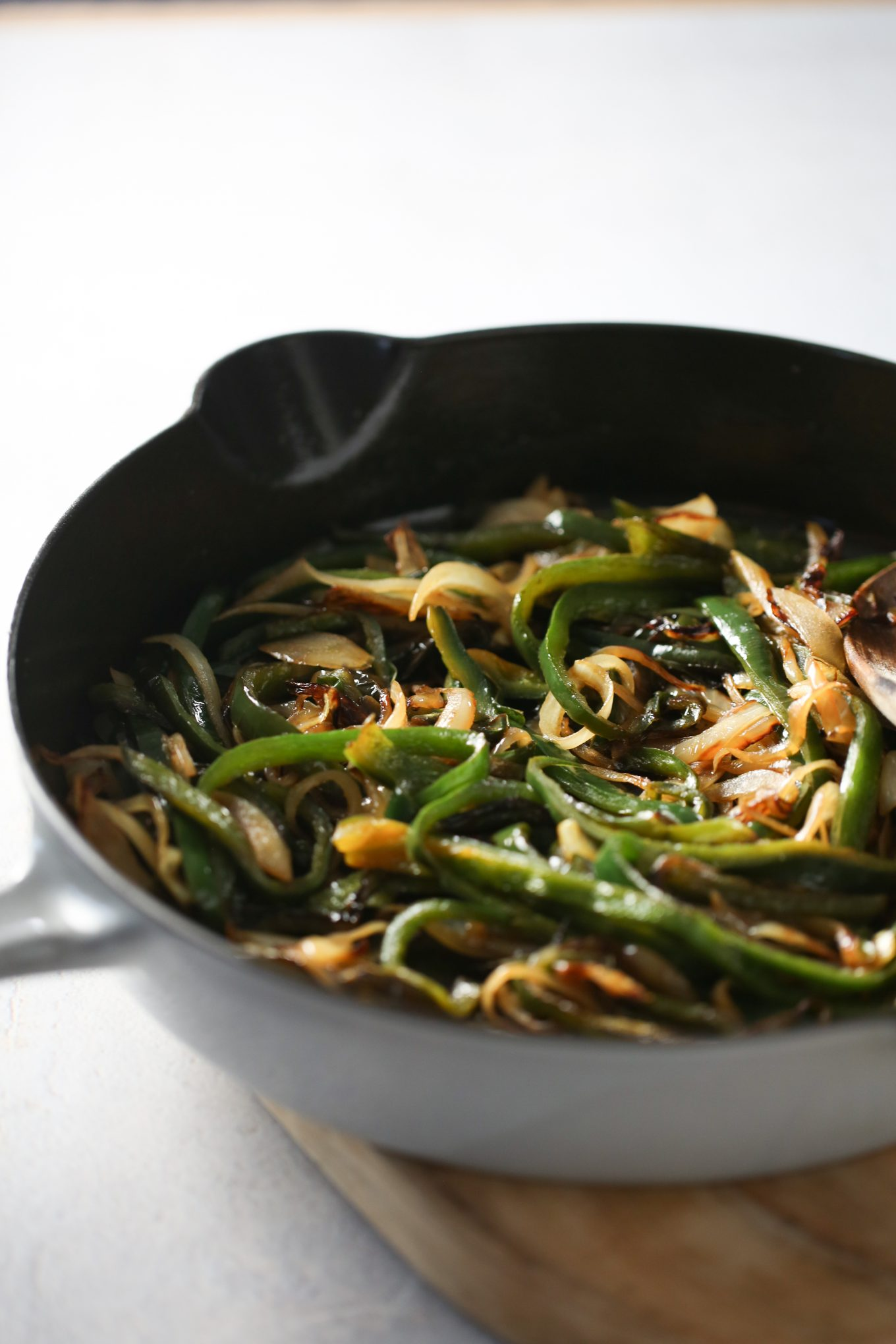 Rasted poblano peppers with onions in an iron cast skillet