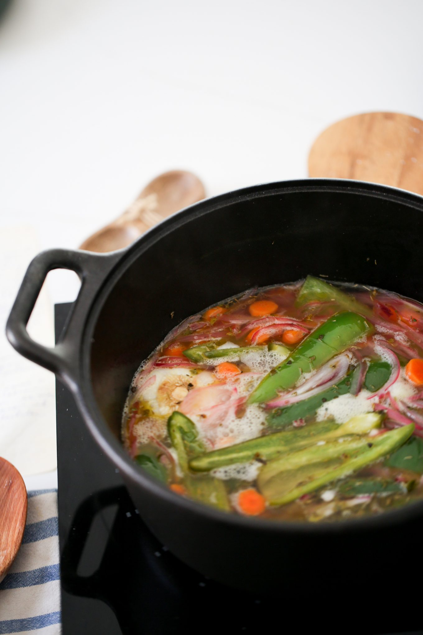 jalapeños, carrots, onions and garlic in a cast iron pot