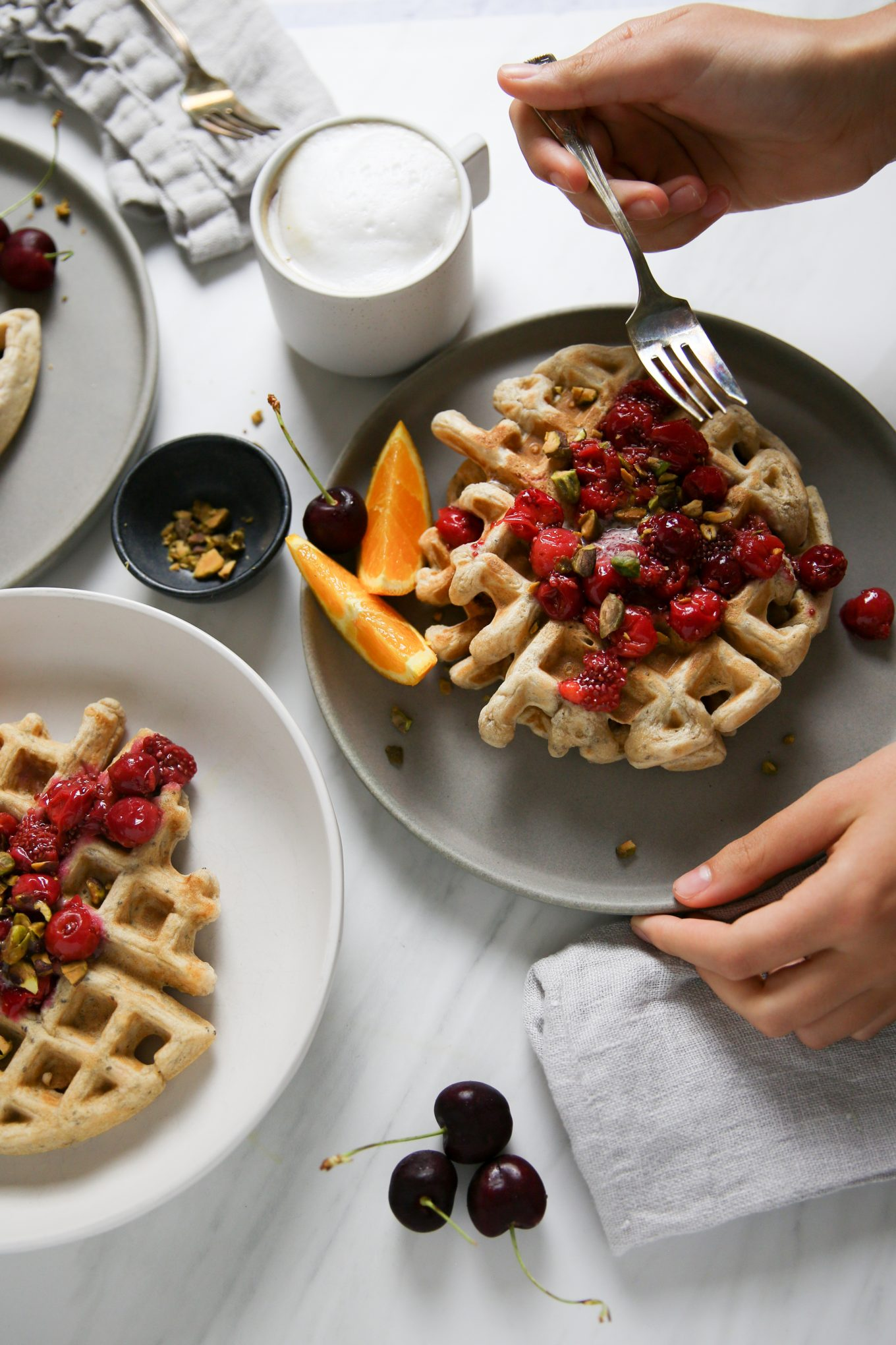 Homemade waffles with cherries and orange slices