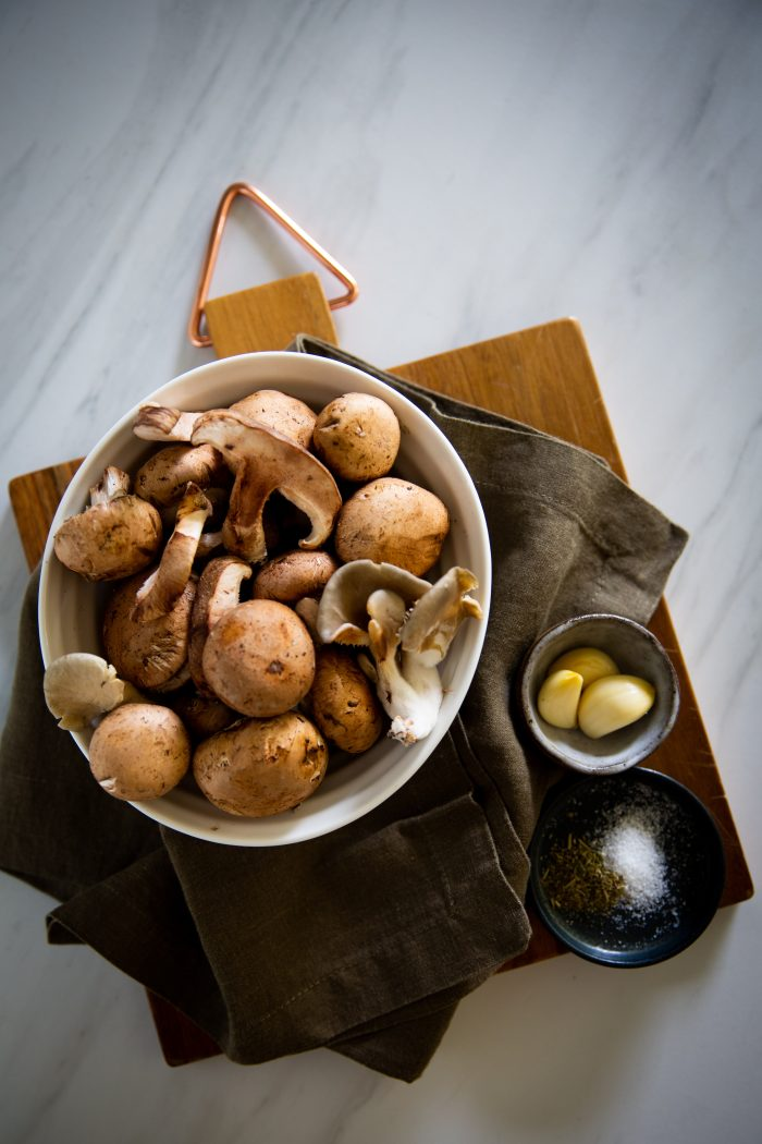 a bowl with different type of mushrooms, garlic and salt ans spices